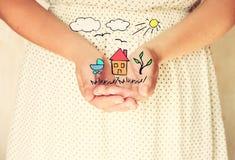Close-up van jonge vrouwenhanden handen uitgestrekt in tot een kom gevormde vorm schetsen van huisboom en vogels als verbeelding  stock foto's