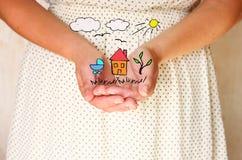 Close-up van jonge vrouwenhanden handen uitgestrekt in tot een kom gevormde vorm schetsen van huisboom en vogels als verbeelding  royalty-vrije stock foto's