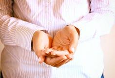 Close-up van jonge vrouwenhanden handen uitgestrekt in tot een kom gevormde vorm Selectieve nadruk royalty-vrije stock afbeelding