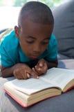 Close-up van jongen die roman thuis lezen Stock Foto