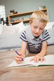 Close-up van jongen het schrijven in boek thuis Stock Foto's