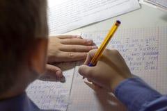 Close-up van jongenshand met potlood die Engelse woorden met de hand op traditioneel wit blocnotedocument schrijven Royalty-vrije Stock Foto's