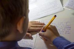 Close-up van jongenshand met potlood die Engelse woorden met de hand op traditioneel wit blocnotedocument schrijven Royalty-vrije Stock Afbeelding