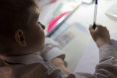 Close-up van jongenshand met potlood die Engelse woorden met de hand op traditioneel wit blocnotedocument schrijven Stock Afbeeldingen