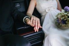 Close-up van jonggehuwdenhanden op de zetel van een auto worden samengehouden die royalty-vrije stock fotografie