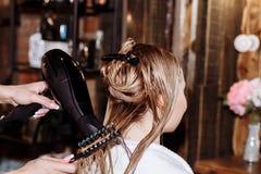 Close-up van kappervrouw die kapsel doen aan cli?nt met lang blondehaar royalty-vrije stock fotografie