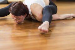 Close-up van Kaukasische Sportieve Vrouw die Yoga doen die binnen praktizeren Het zitten in Rug en Benen Gescheiden Gespleten Uit royalty-vrije stock fotografie