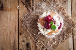 Close-up van kersenmuffin met kruimelig bovenste laagje op houten achtergrond, hoogste mening royalty-vrije stock fotografie