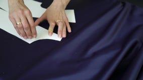 Close-up van keurige handen van het vrouwelijke malplaatje van de kleermakerstekening op stof met krijt stock videobeelden