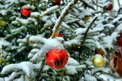 Close-up van kleurrijke Kerstmisballen onder sneeuwvlokken in sneeuw met CH Royalty-vrije Stock Foto