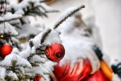 Close-up van kleurrijke Kerstmisballen onder sneeuwvlokken in sneeuw met CH Royalty-vrije Stock Afbeelding