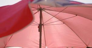 Close-up van kleurrijke paraplu die tegen duidelijke blauwe hemel golven stock footage