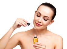 Close-up van kosmetische olie wordt geschoten die op jong vrouwen` s gezicht dat van toepassing zijn stock foto