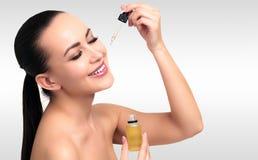 Close-up van kosmetische olie wordt geschoten die op jong vrouwen` s gezicht dat van toepassing zijn stock afbeelding