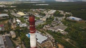 Close-up van lange, rode en witte die schoorsteen-steel boven de industriezone en fabrieksgebouwen door groen bos worden omringd stock videobeelden