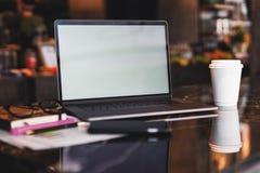 Close-up van laptop met lege monitor en kop van koffie op lijst in koffie Lege werkplaats zonder mensen Huisbureau freelancer royalty-vrije stock foto