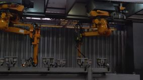 Close-up van lassen van metaaldelen door lassenmachine bij fabriek scène Grote industriële robot-lassers van metaalauto stock video