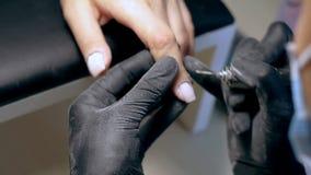 Close-up van manicure die hardwaremanicure doen aan een jong meisje in de kuuroordsalon stock video