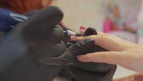 Close-up van manicure die het oude gelpoetsmiddel verwijderen die elecrtric nagelvijl met behulp van stock video