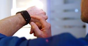 Close-up van mannelijke directeur die slim horloge met behulp van stock video