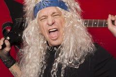 Close-up van mannelijke gitarist die op middelbare leeftijd over gekleurde achtergrond schreeuwen royalty-vrije stock afbeeldingen