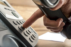 Close-up van mannelijke hand die een telefoonnummer op zwarte landlin draaien stock afbeeldingen