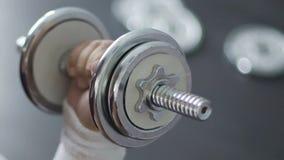 Close-up van mannelijke hand die zware domoor bij sportclub proberen op te heffen, motivatie stock videobeelden