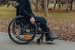 Close-up van mannelijke hand op wiel van rolstoel tijdens gang in park royalty-vrije stock afbeeldingen