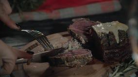 Close-up van mannelijke handen die mes en vork gebruiken terwijl de snijdende eerste beet van heerlijke biefstuk met geroosterd d stock video