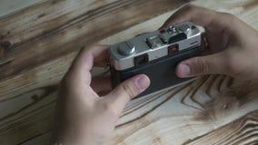 Close-up van mannelijke handen geplaatst nieuwe film Wijnoogst 35mm Camera SLR Afstandsmetercamera stock video