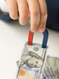 Close-up van mannelijke handholding magneet en het trekken van geld van stapel Stock Afbeeldingen