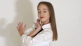 Close-up van meisje in het lange stromende haar stellen in een ruimte met een witte muur stock video
