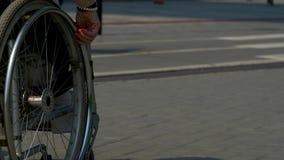 Close-up van meisjeshand het draaien wielen op zijn rolstoel stock videobeelden