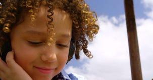 Close-up van mengen-rasschoolmeisje het luisteren muziek op hoofdtelefoons in de schoolspeelplaats 4k stock footage