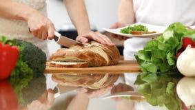 Close-up van Menselijke handen die in keuken koken Moeder en dochter of twee vrouwelijke vrienden die brood voor diner snijden stock afbeelding