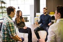 Close-up van mensen die terwijl het zitten in cirkel en het gesturing communiceren Stock Fotografie