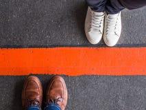 Close-up van mensen door een rode lijn wordt verdeeld die stock afbeelding