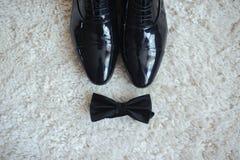 Close-up van mensen` s schoenen en een vlinderdas Allen in zwarte royalty-vrije stock foto's