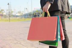 Close-up van mensenholding het winkelen zakken met status bij het autoparkeerterrein royalty-vrije stock afbeeldingen