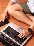 Close-up van mensenzitting het typen op keybord van zijn laptop en zijn smartphone gelijktijdig stock foto