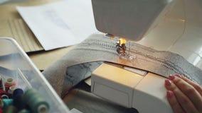 Close-up van modern elektrisch naaimachine het werk het stikken stuk van textiel Het meisje ` s manicured hand en het kleurrijke  stock videobeelden