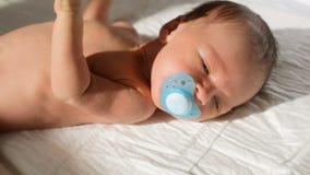 Close-up van moeder wordt geschoten die soother aan haar pasgeboren babyzoon geven die op bed in zonstralen die liggen stock videobeelden