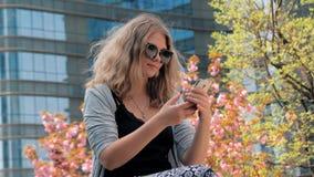 Close-up van mooi jong Europees meisje in zonnebril die op de straat zitten en selfie door smartphone maken met stock videobeelden