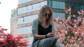 Close-up van mooi jong Europees meisje in zonnebril die op de straat zitten en smartphone met binnen wolkenkrabbers gebruiken stock videobeelden