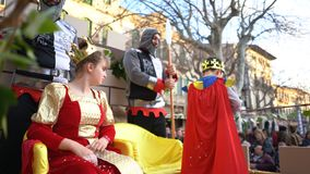 Close-up van mooi jong meisje in de zitting van het koninginkostuum op de troon dichtbij twee ridders en jongen in mantel en kroo royalty-vrije stock afbeelding