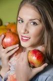 Close-up van mooi meisje die twee granaatappels houden stock foto's