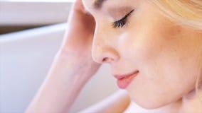Close-up van mooie blondevrouw met diepe blauwe ogen en perfecte make-upzitting bij de badkamers en het denken over stock foto