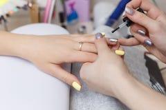 Close-up van mooie handen die transparant nagellak in schoonheidssalon toepassen De Spijkers van manicurehand painting client ` s stock foto