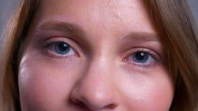 Close-up van mooie jonge Kaukasische vrouwelijke blauwe ogen die en camera openen bekijken stock videobeelden