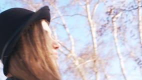 Close-up van mooie jonge vrouw in een donkere hoed en zwart leerjasje met modieuze make-up die camera in de lente bekijken stock footage